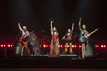 A production shot of five members of a band, their arms raised and pointed to the sky